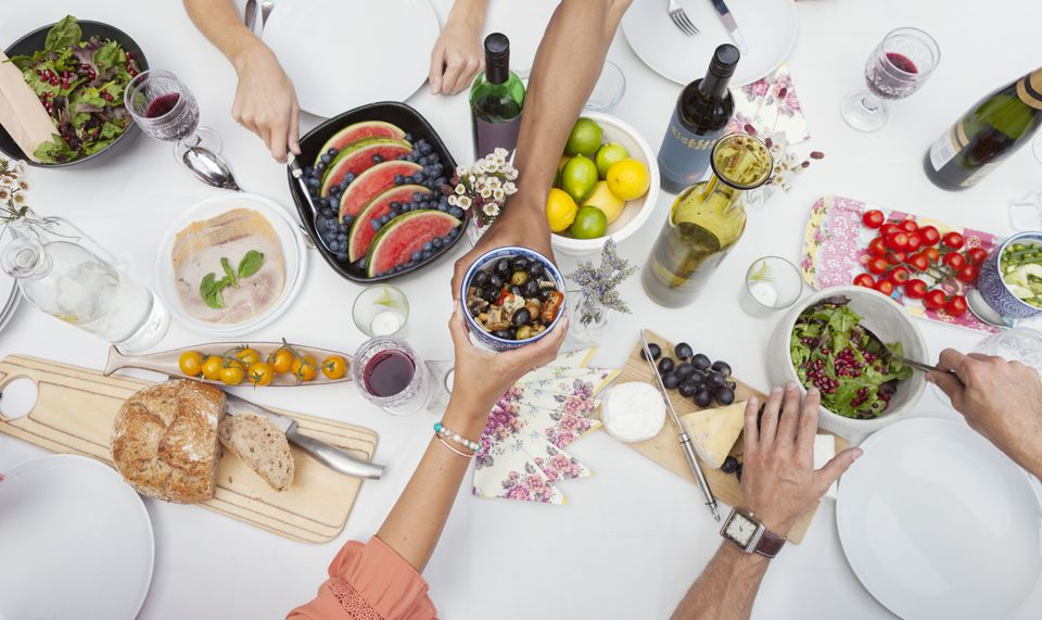 Overhead view of friends enjoying garden party lunch on patio table