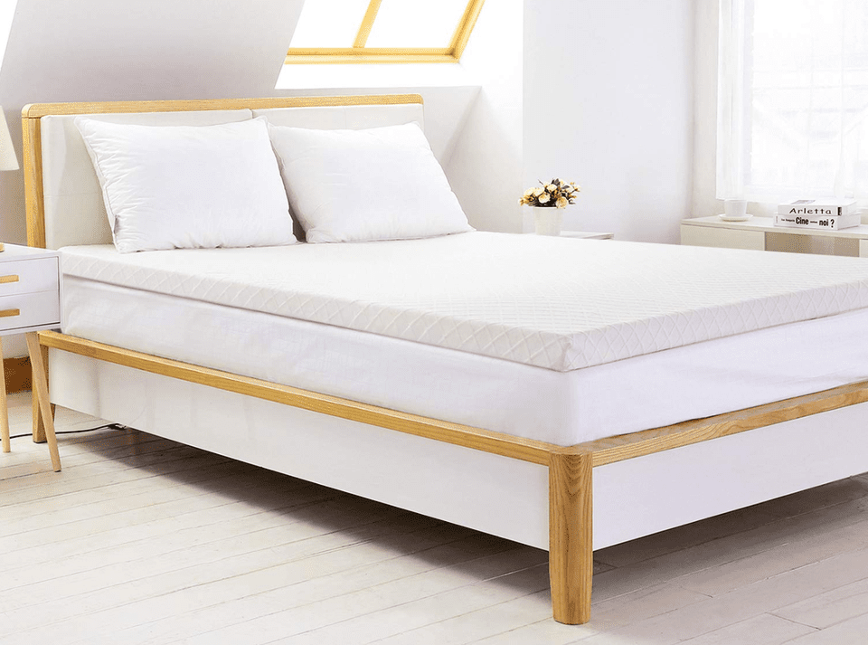 White mattress pad on a bed in a well-lit room