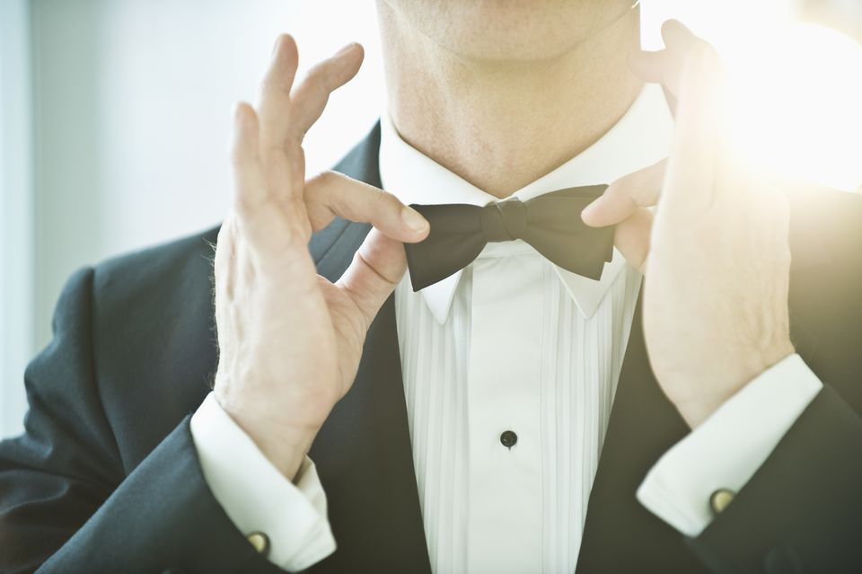 A man in a tuxedo fixing his bowtie