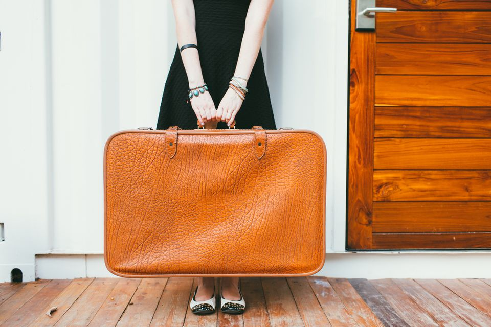 Low Section Of Woman Holding Suitcase On Hardwood Floor