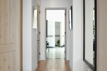 A hallway with a mirror on the wall in home