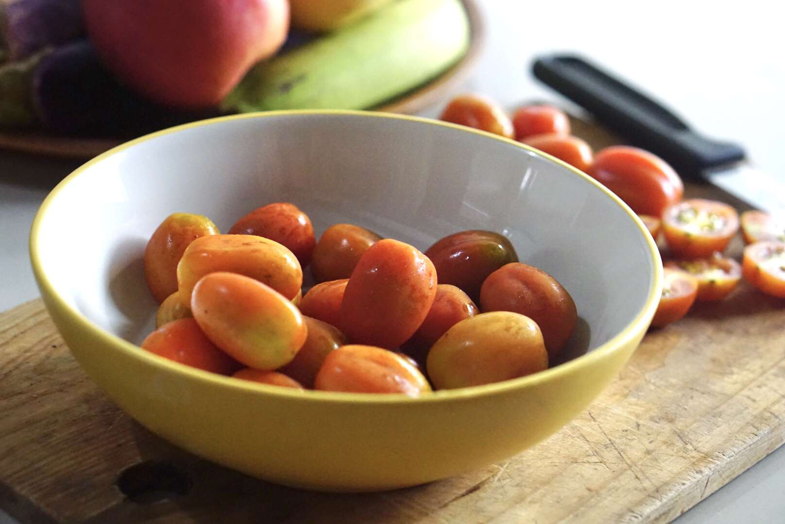 Red and orange cherry tomatoes in a yellow bowl on wood cutting board