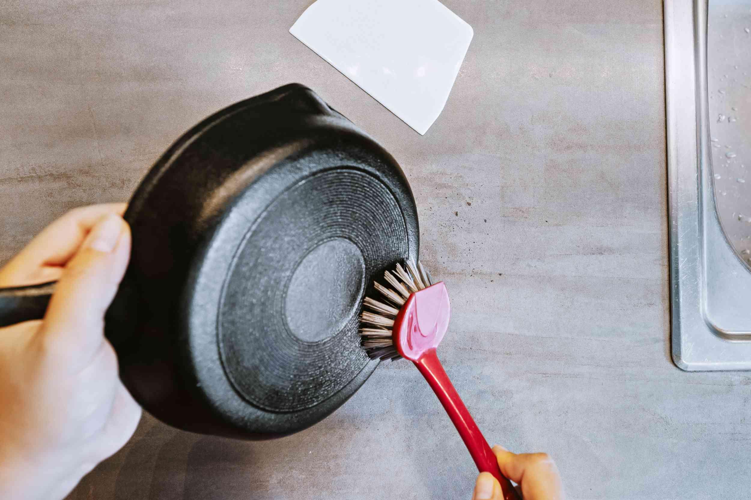 Stiff-bristled nylon brush scraping away rust from bottom of cast iron griddle pan