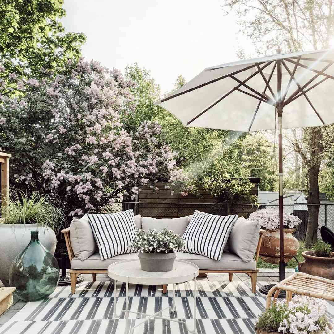 A spring inspired outdoor living room with an umbrella, love seat and rug.