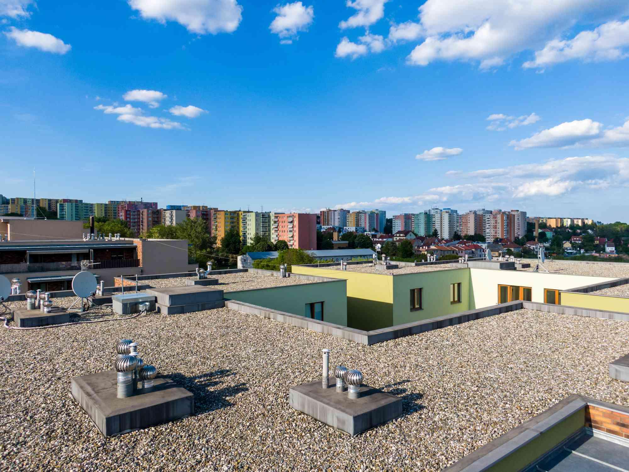 Vista aérea del techo plano de la casa en un edificio residencial. Exterior de arquitectura moderna. Sistemas de aire acondicionado y estructura de ventilación. Edificio residencial en el fondo, día soleado