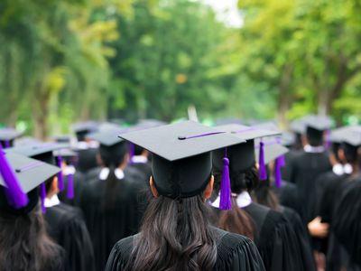 Back of graduates during commencement at university. Close up at graduate cap.