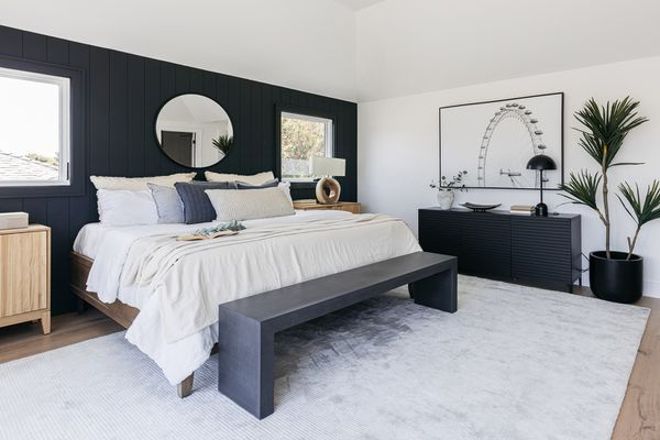 Decorated bedroom with navy blue walls, dresser and bench surrounding a white bed