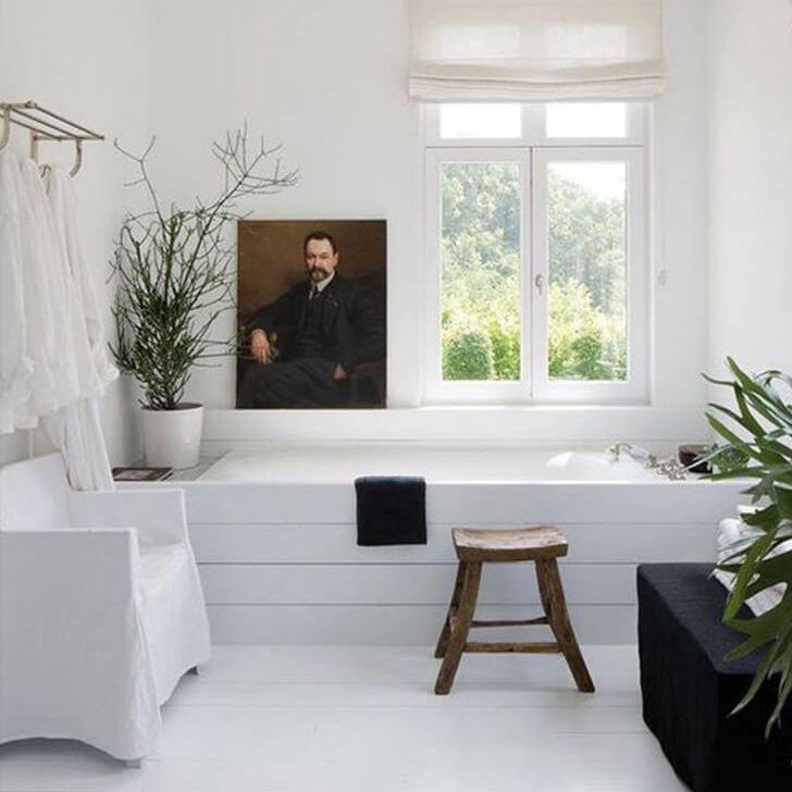 baño con una pintura al lado de la bañera