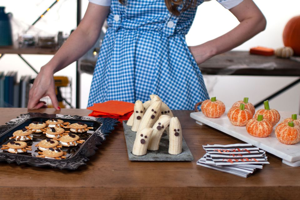 Woman standing behind table of Halloween snacks