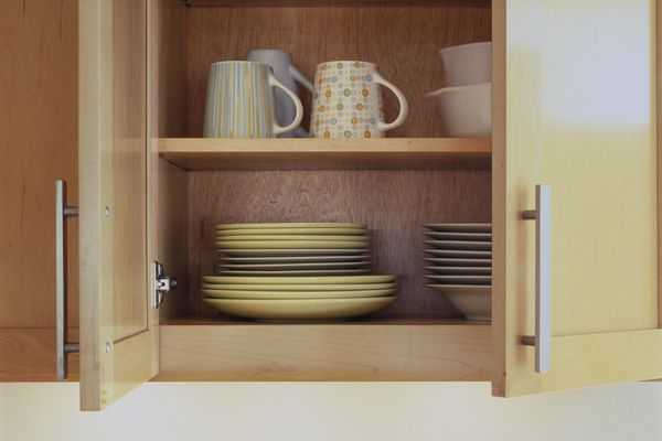 Close-up of dishes in an open kitchen cabinet.