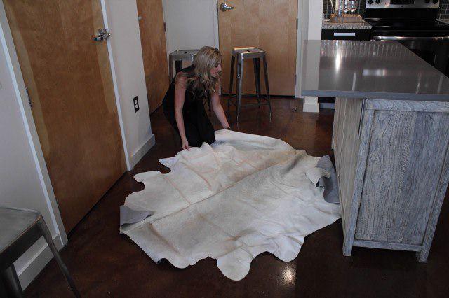 Mujer colocando una alfombra blanca sobre pisos de concreto en una cocina