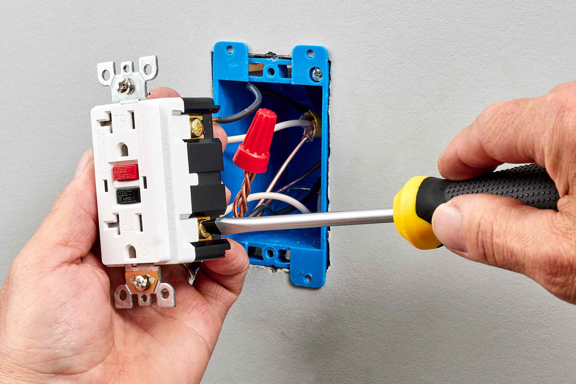 GFCI receptacle replacing a standard outlet with screwdriver