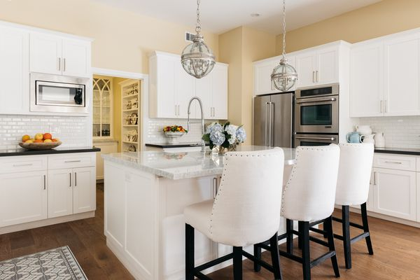 French country stylized kitchen with white cabinets, vintage white chairs hanging globe lights