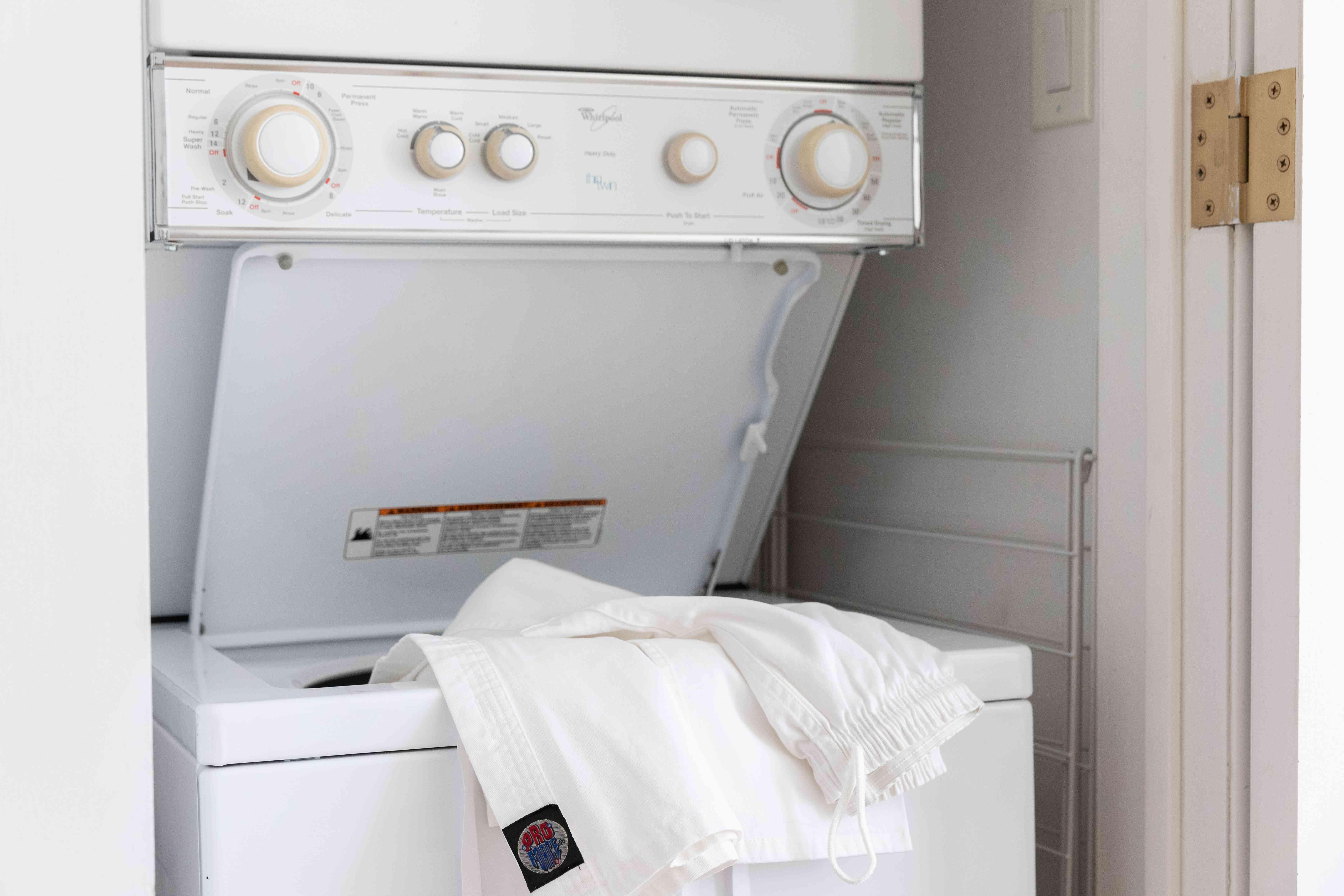 Karate uniform hanging off edge of open washing machine