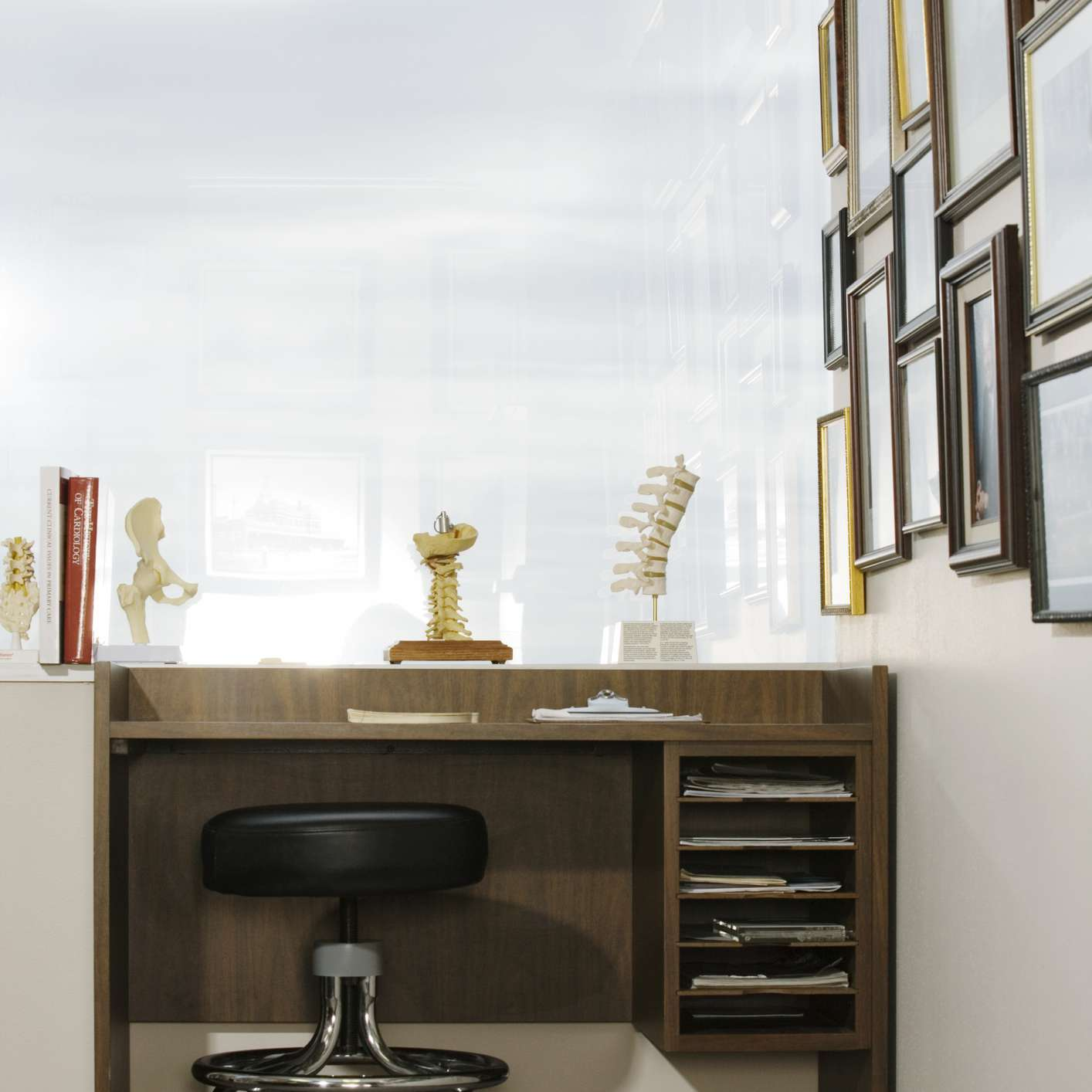 Doctor's desk by window, diplomas on wall