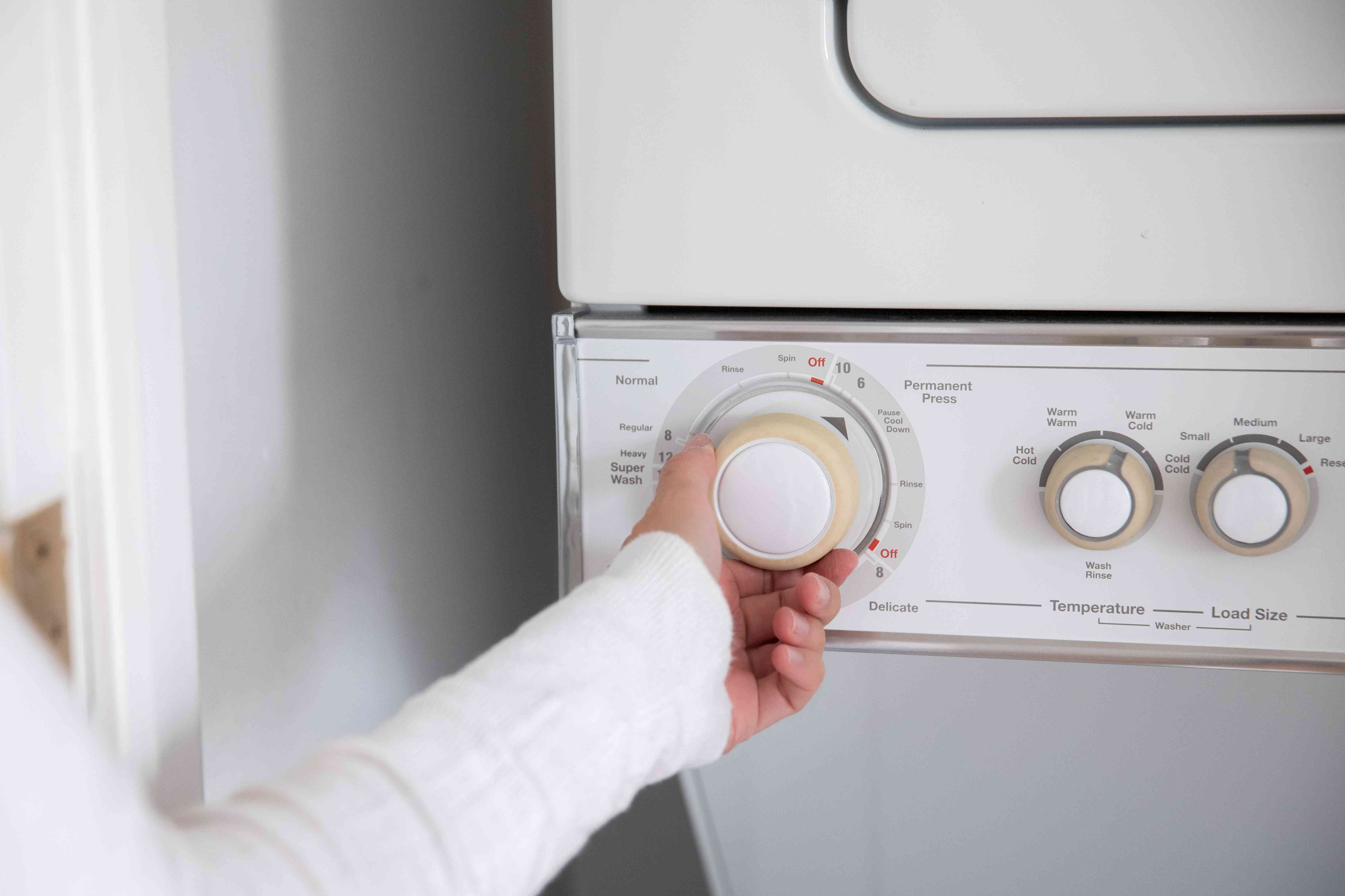 Someone selecting a washer temperature