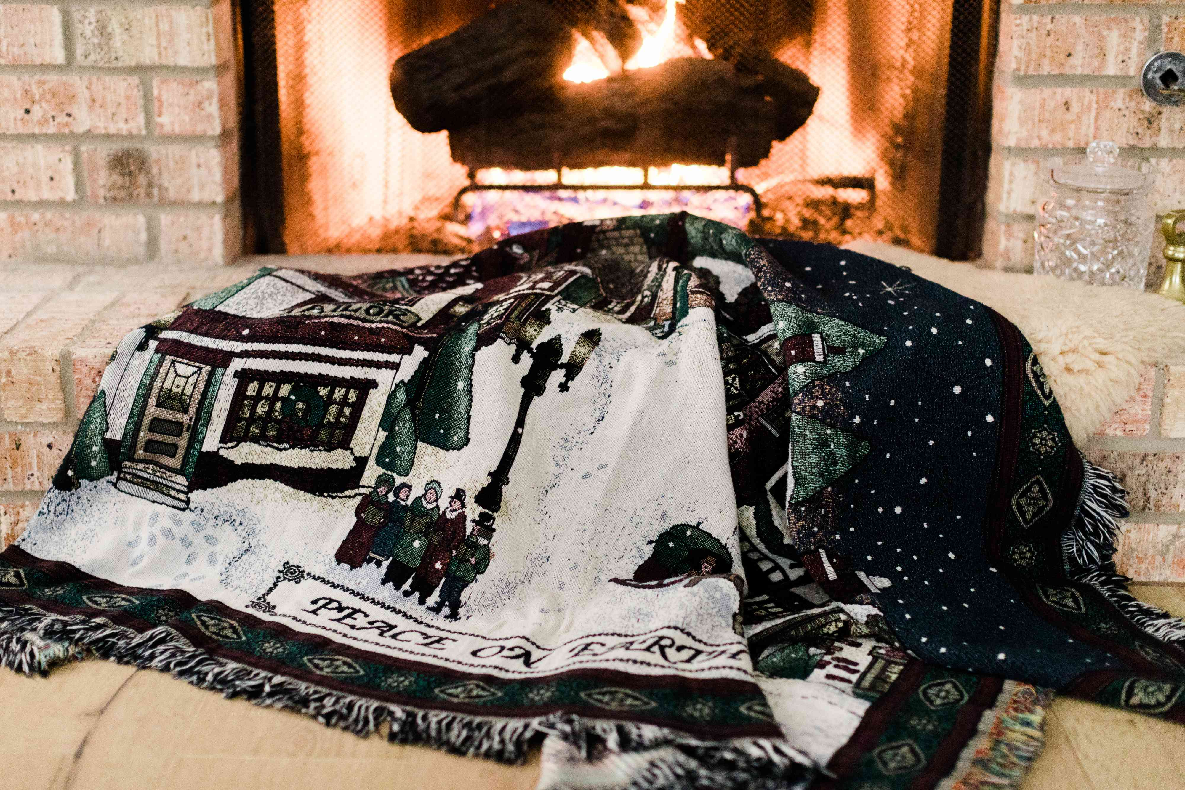 Christmas blanket laying on floor in front of lighted fireplace