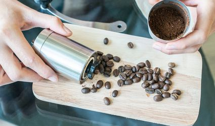Male hands holding a coffee grinder and coffee beans on wooden board