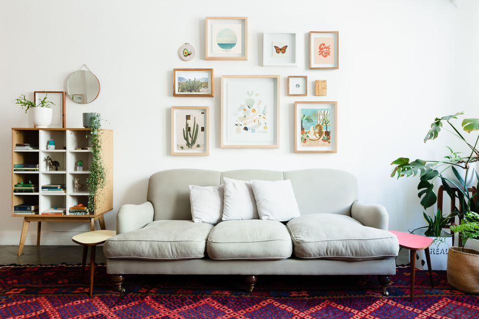 Eclectic gallery wall above light gray couch in decorated living room with houseplants