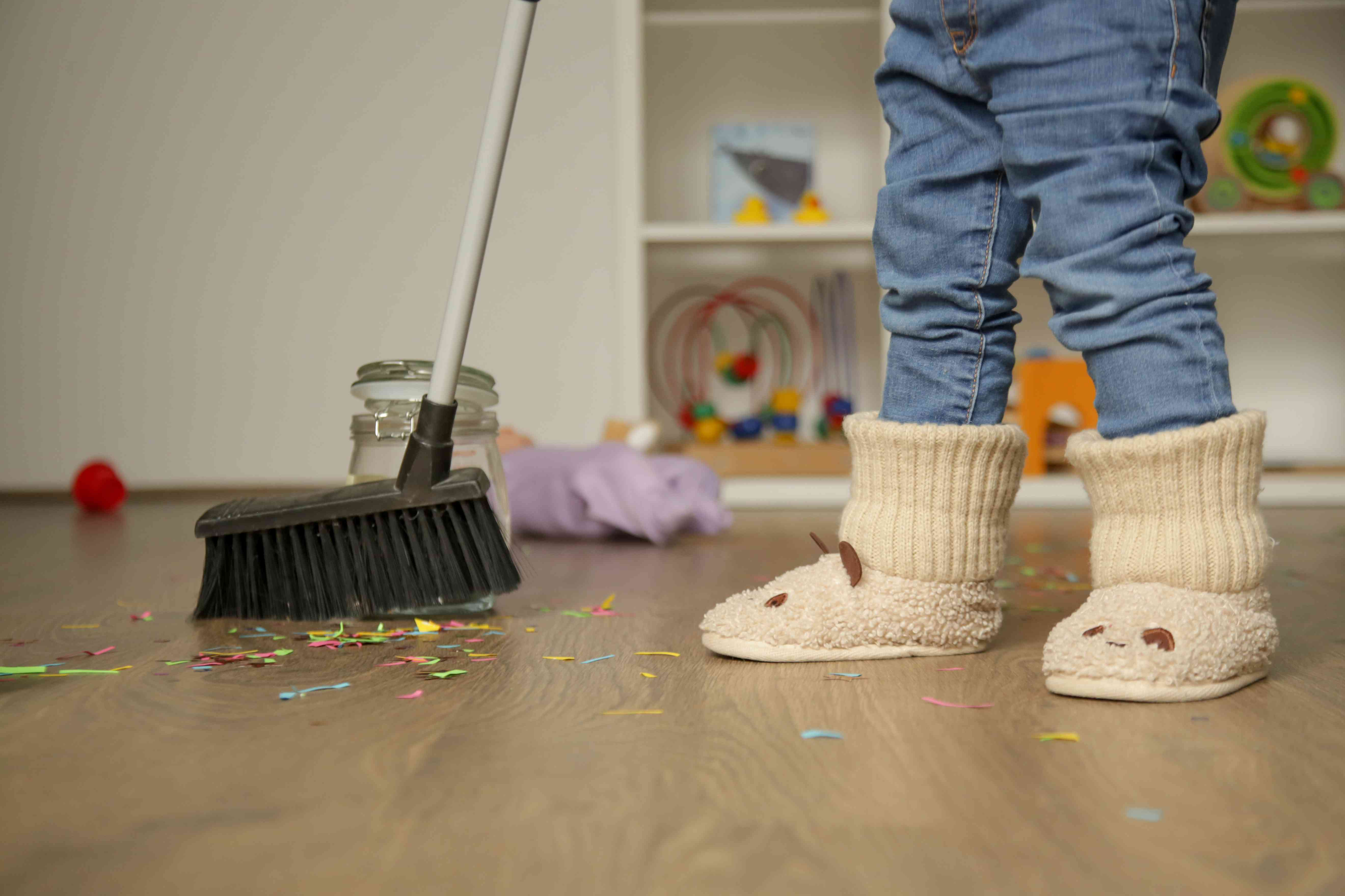 Adorable blonde toddler girl playing with broom, cleaning colorful confetti from the floor