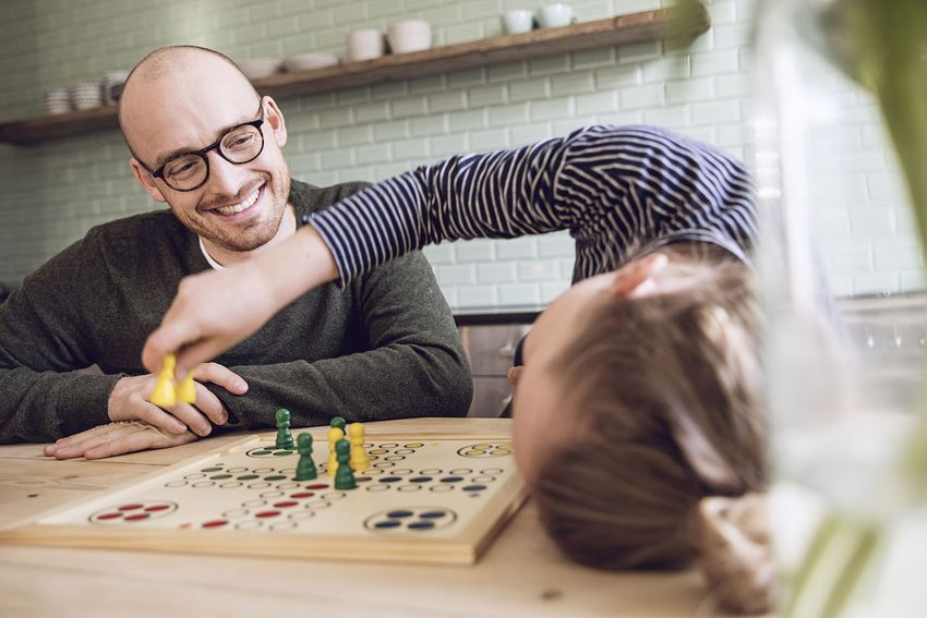 Father and daughter playing board game in the kitchen