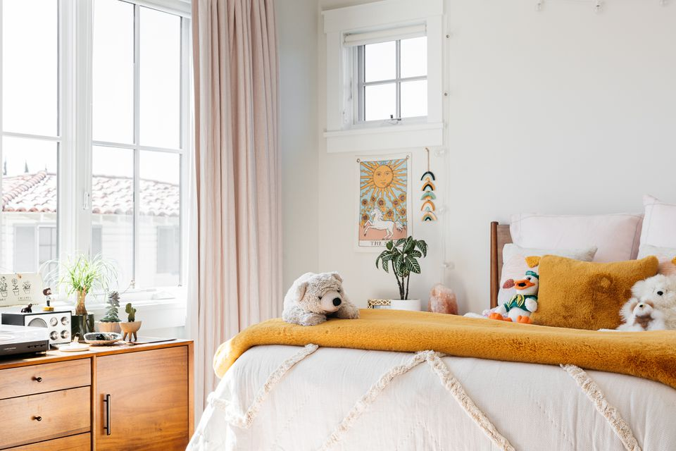 Bright bedroom with yellow folded blanket on bed with stuffed toys and wooden dresser next to window