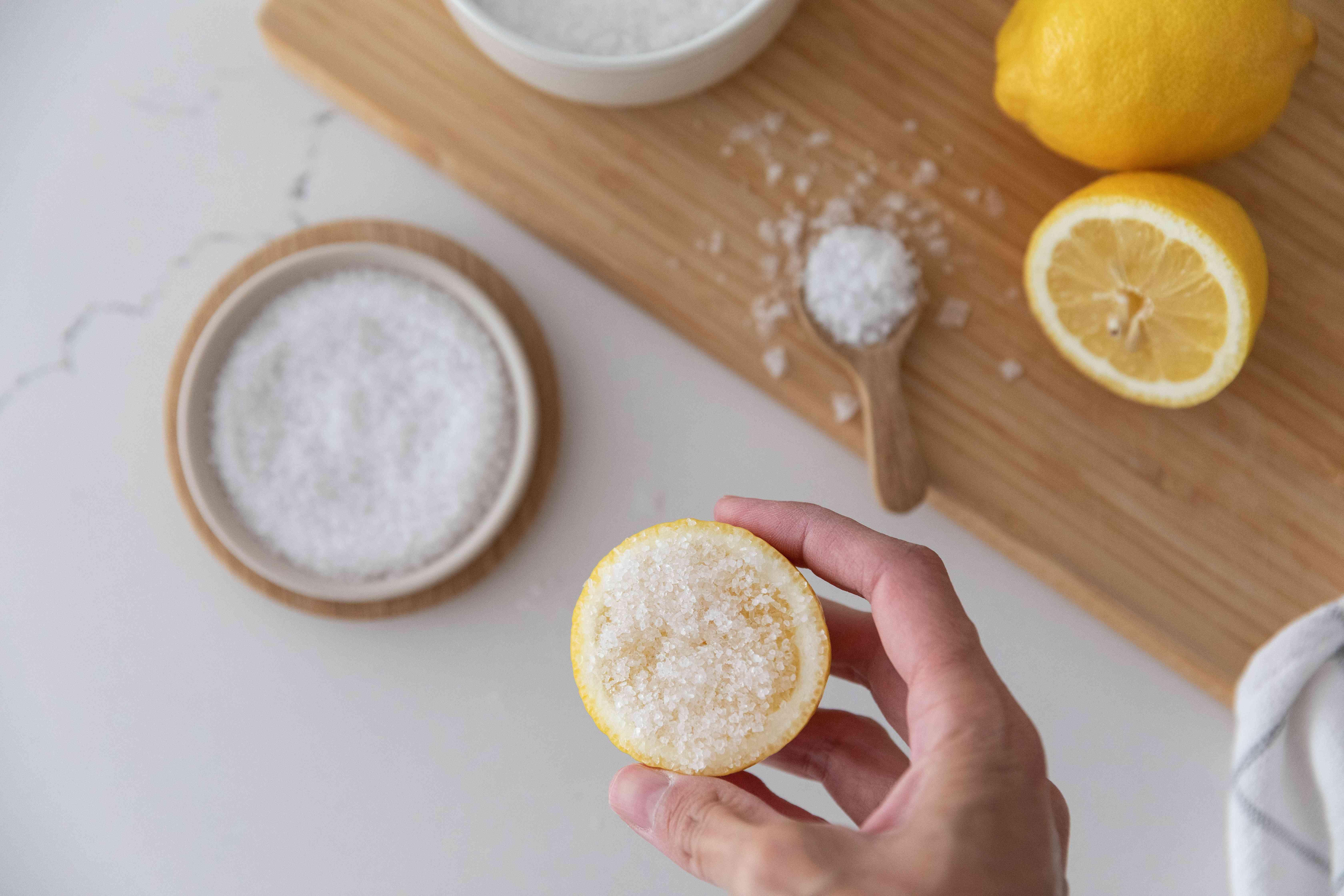 Salt rubbed on lemon half above bowl of salt and cut lemons