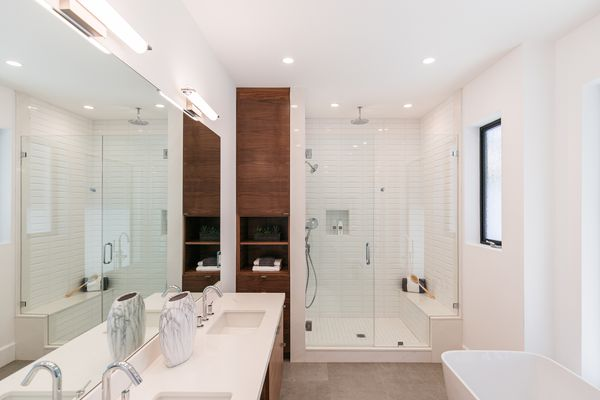 Modern bathroom with wood cabinet surrounded by white walls and countertops
