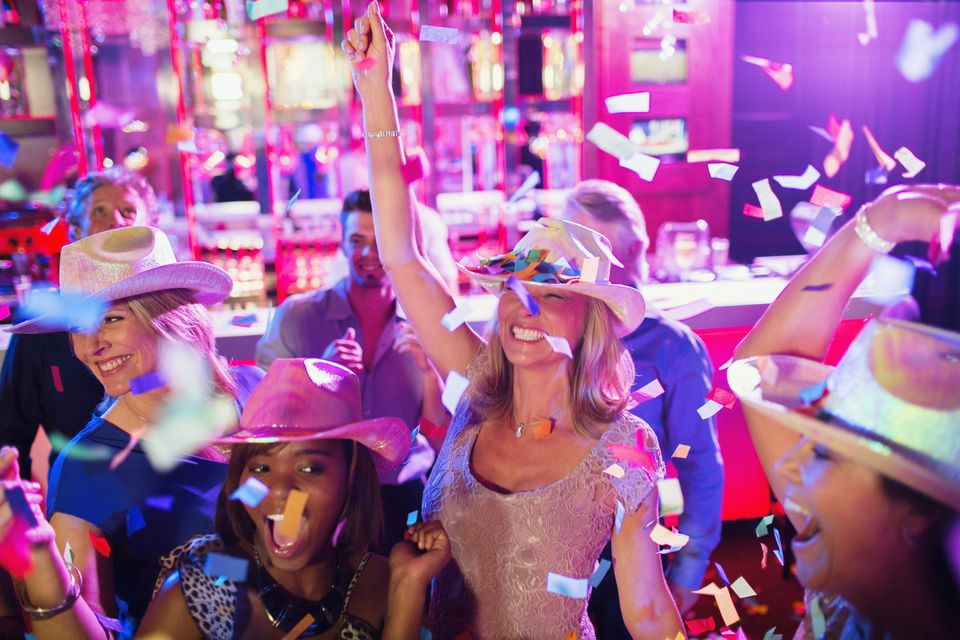 Confetti falling on women wearing cowboy hats dancing in nightclub