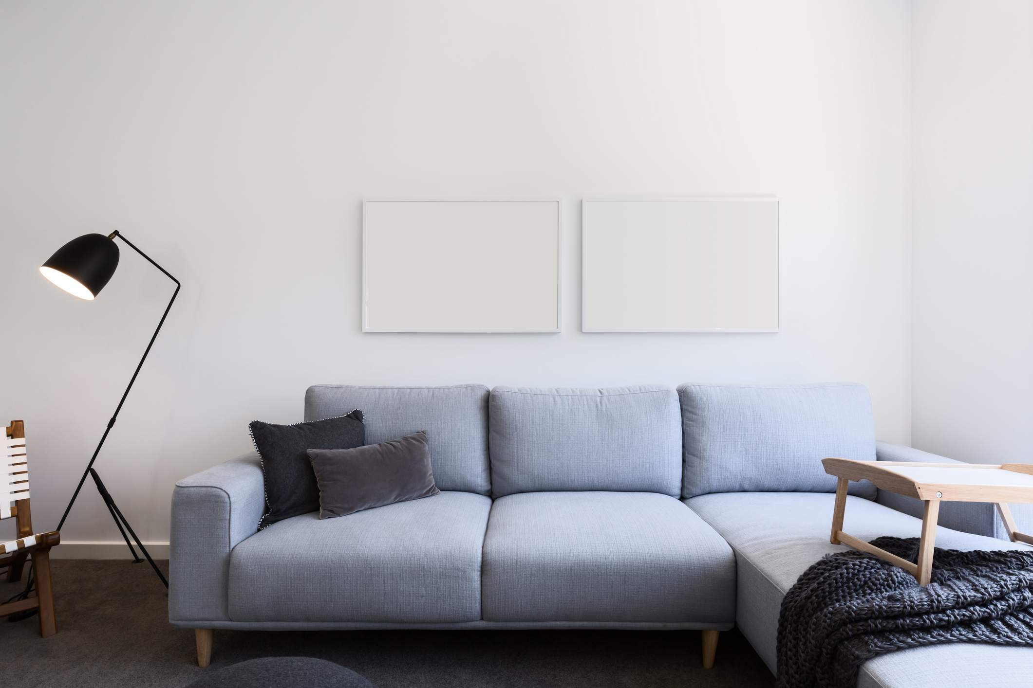 Charcoal pillows and blanket on pale blue couch