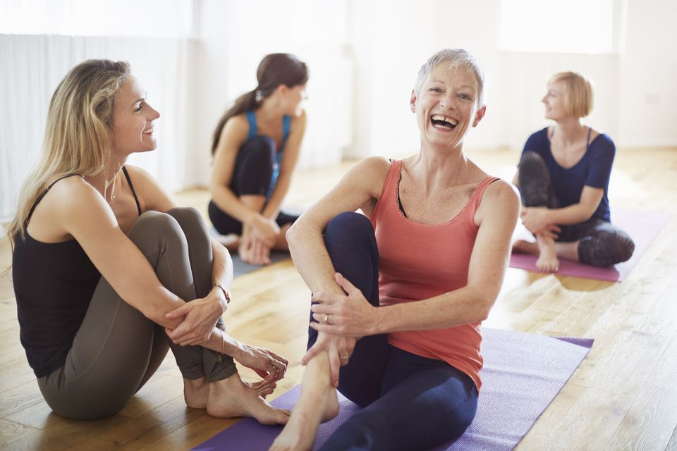 Four women sitting on yoga mats, laughing and talking while wearing yoga attire.