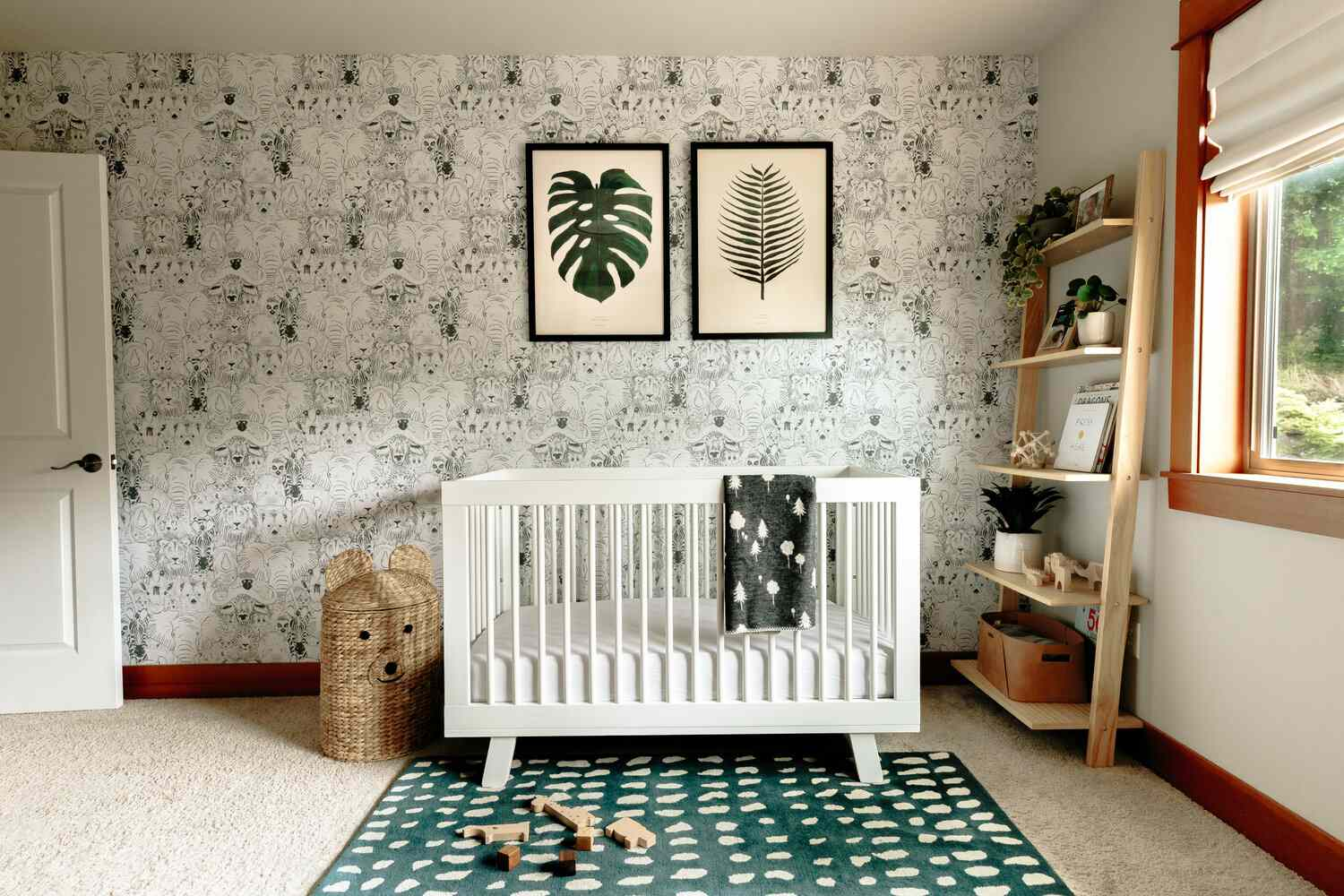 white crib in room with pattern wallpaper, leaf artwork on wall