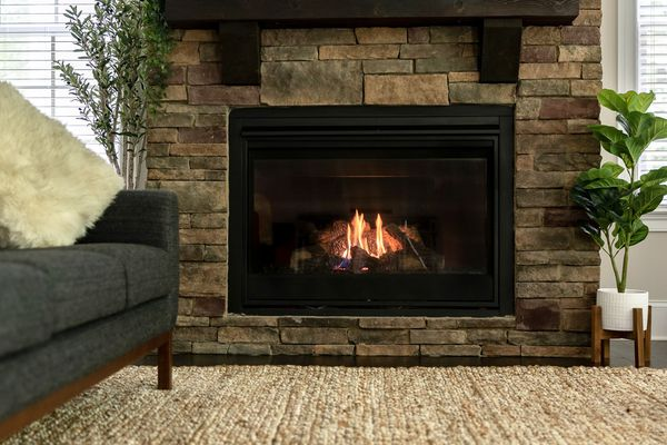 Ventless gas fireplace decorated with surrounding bricks, houseplants and couch
