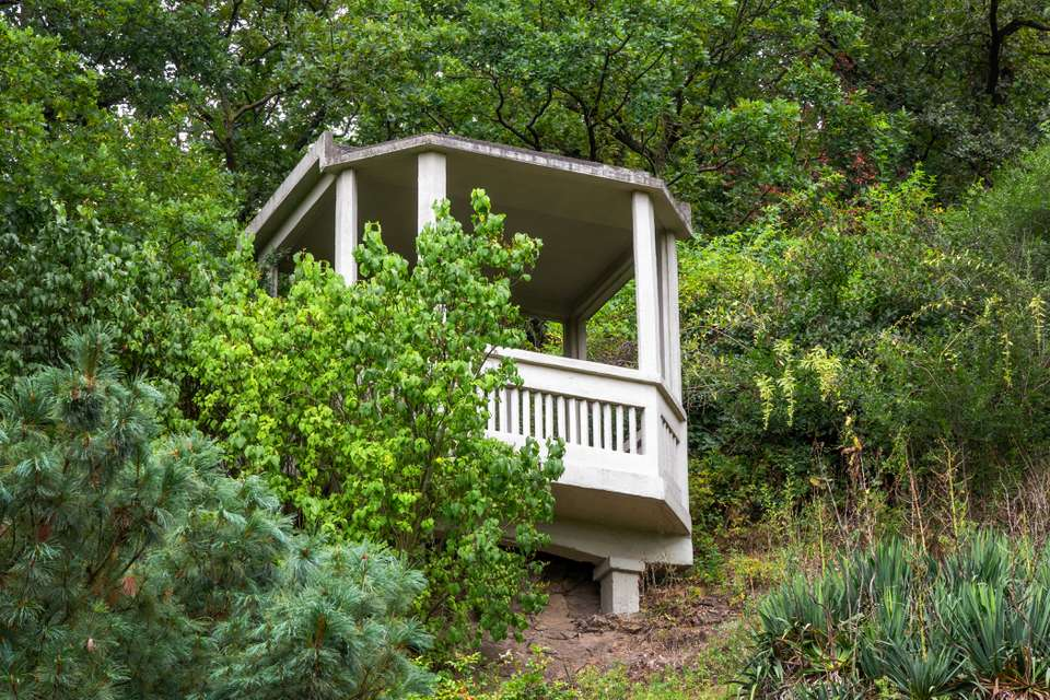 White gazebo on side of hill surrounded by trees and shrubs