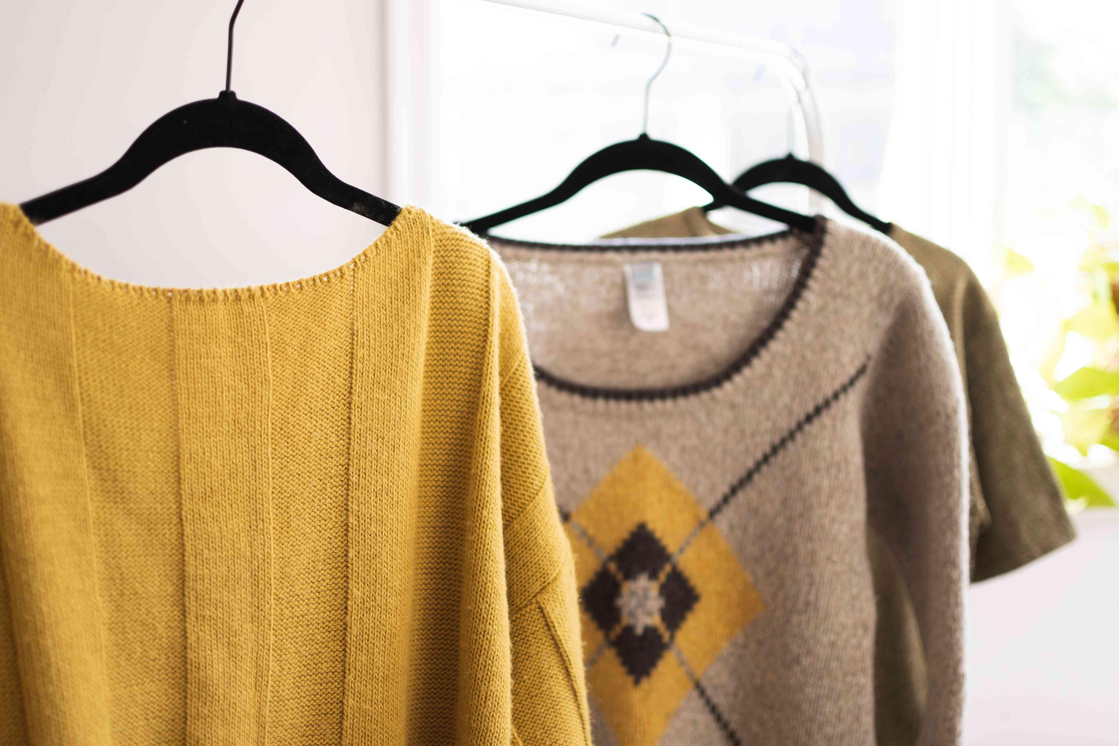 Yellow and beige acrylic sweaters hanging on black hangers