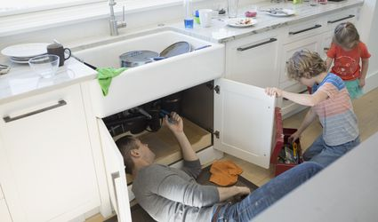Father and son fixing pipe under kitchen sink