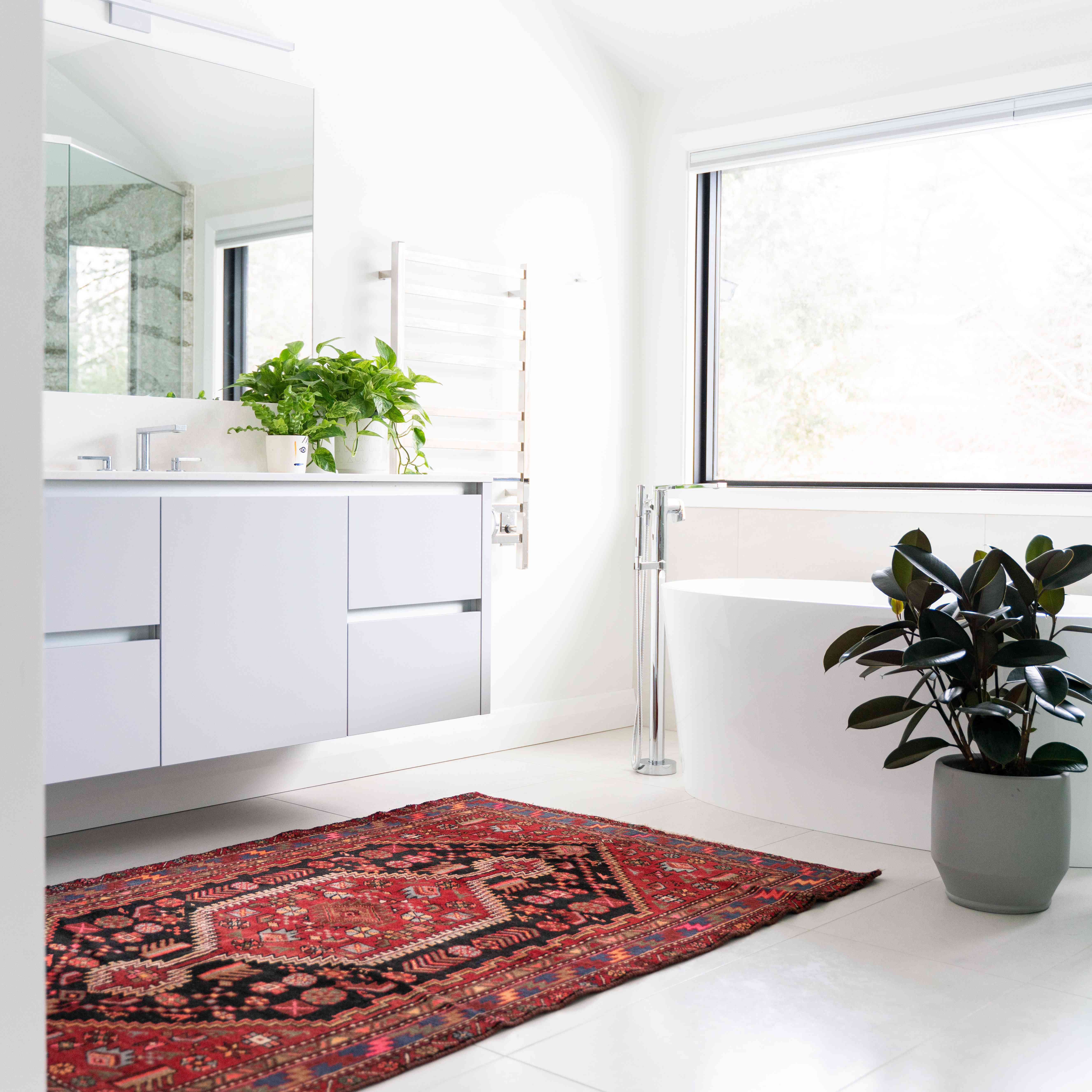 White spacious bathroom with a red rug and plants