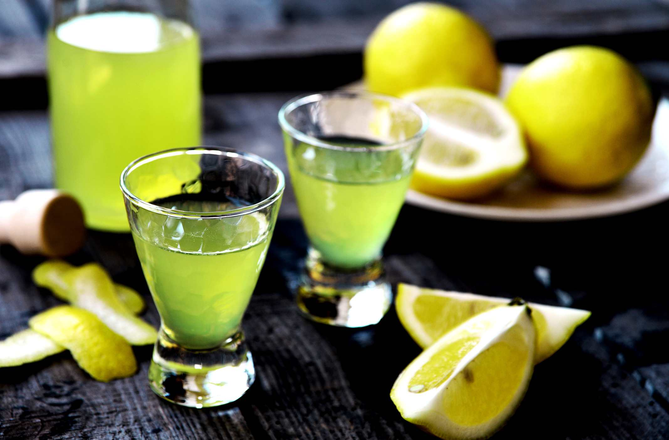 Shots of Limoncello with lemon wedges.