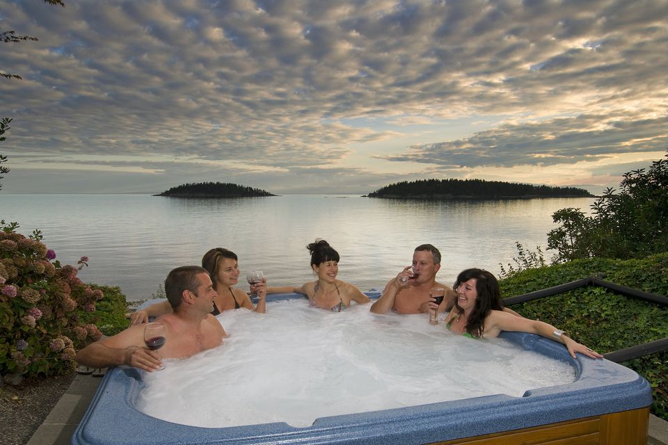 Group of people in hot tub on beach.