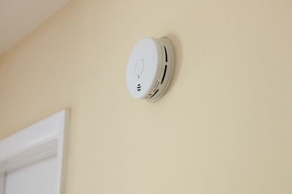 Fire and smoke detector on beige wall