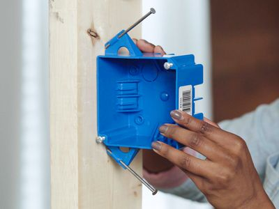 Electrical junction box being nailed to wooden post for installation