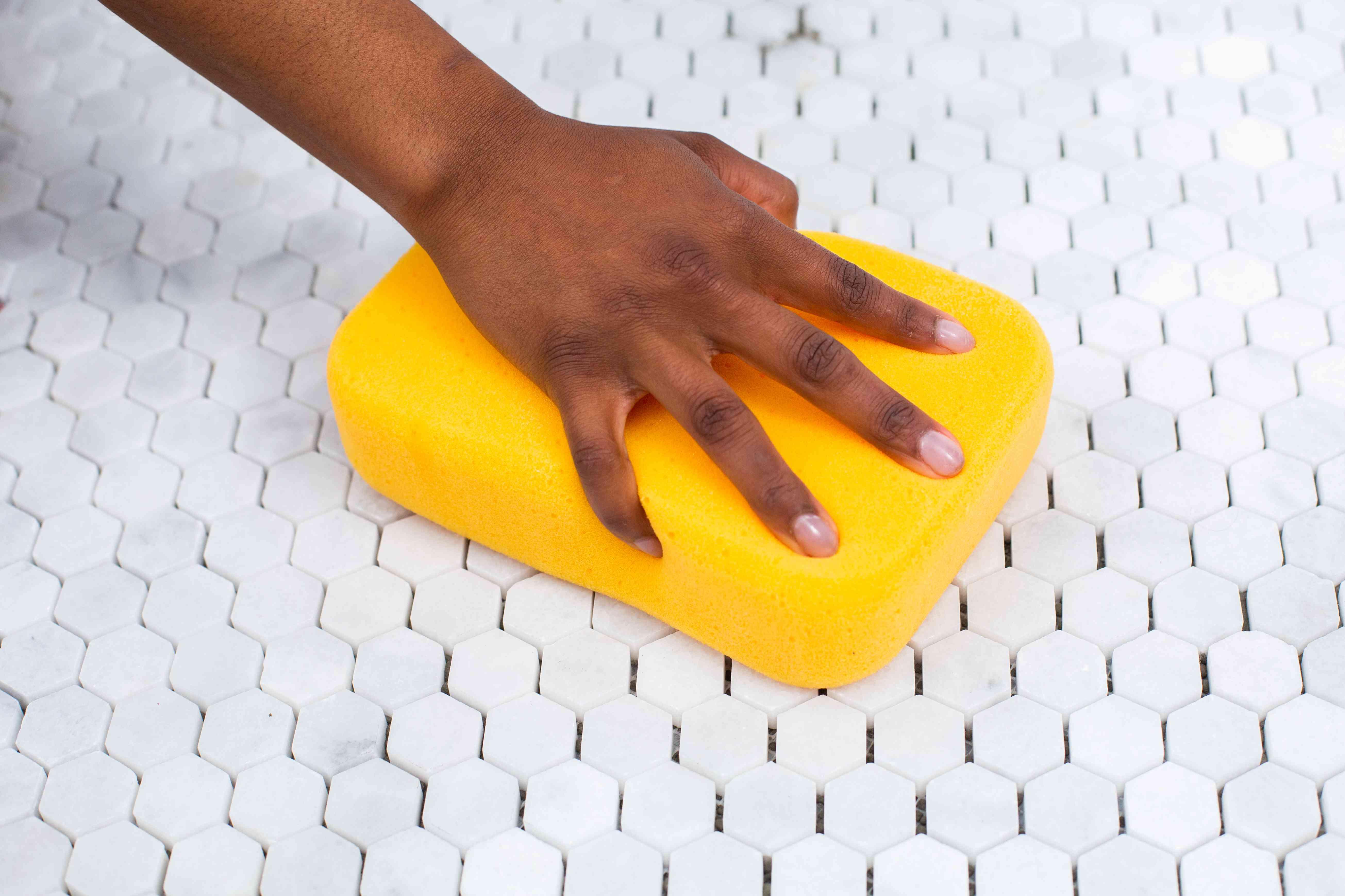 Grout sponge passing over white geometric tiles