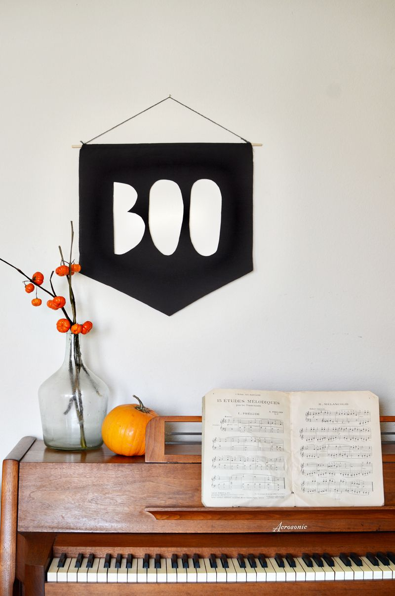 A black and white boo banner above a piano