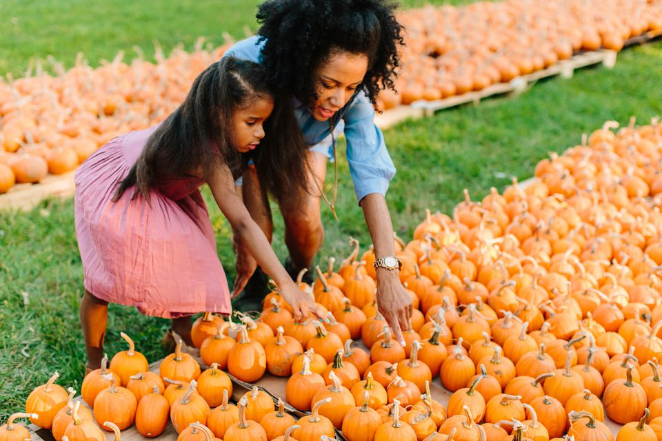 mom and daughter picking out a pumpkin at the pumpkin patch