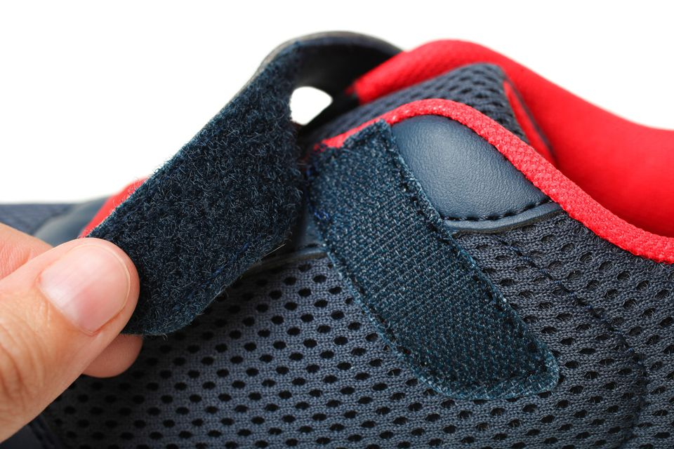 Hand opening Velcro closure on navy and red tennis shoes