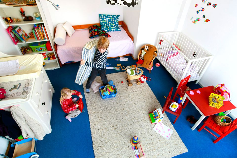 Children cooperating to clean a messy nursery bedroom