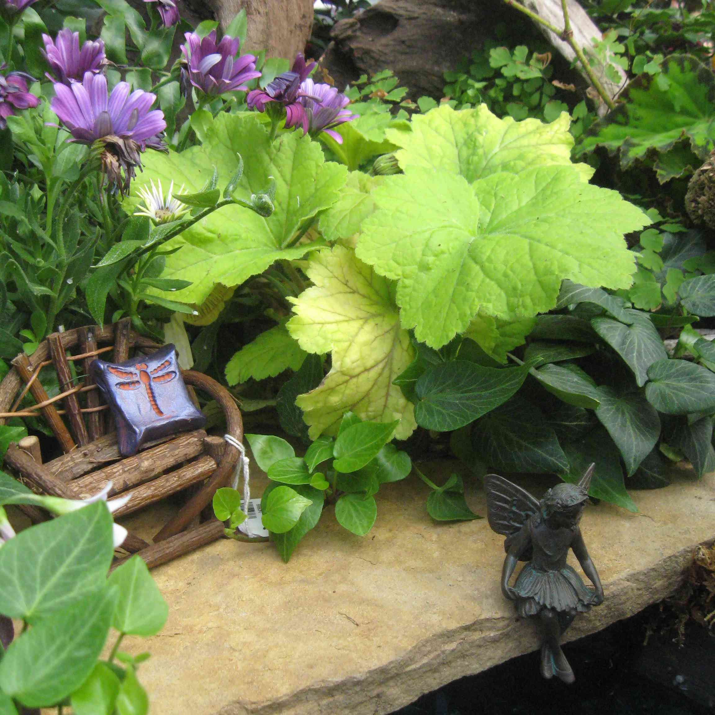 Miniature bench and fairy statue among plants.