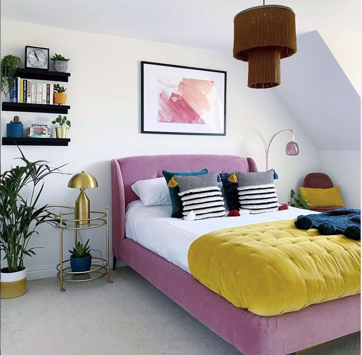 bedroom with white walls, light purple bed frame, yellow comforter, accents of gold and purple glass