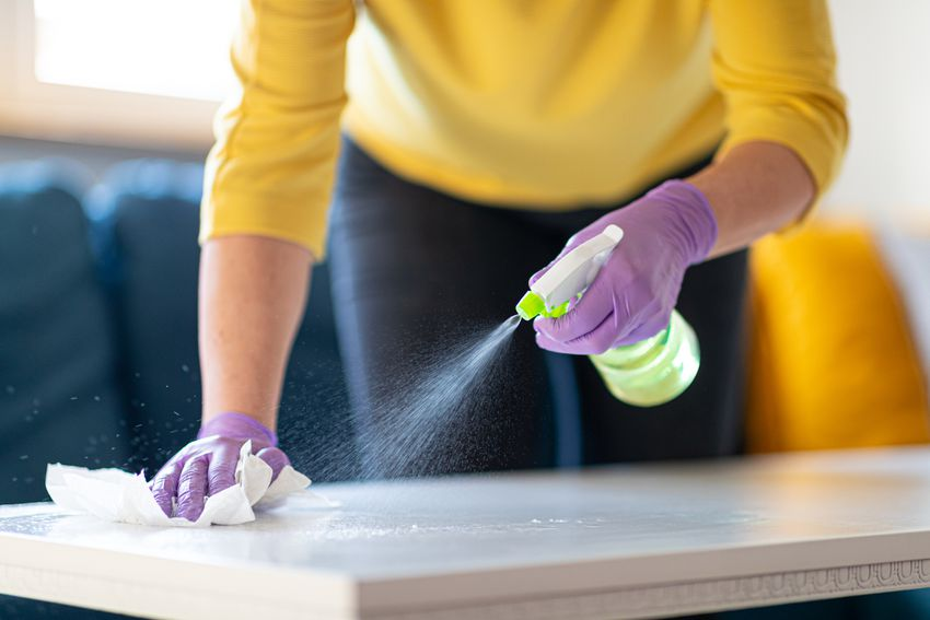 Hands in gloves disinfecting coffee table.