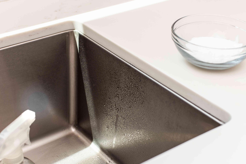 Distilled white vinegar sprayed on stainless steel sink to but through mineral deposits